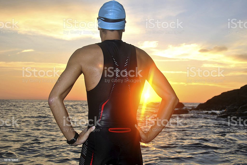 young athlete triathlon in front of a sunrise stock photo
