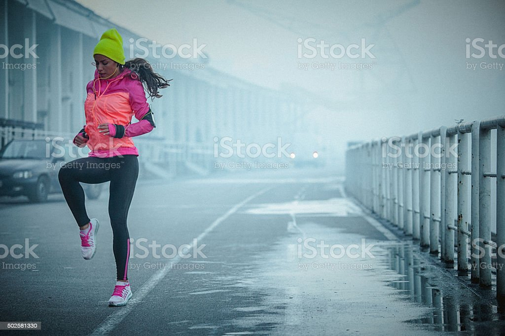 Young athlete woman exercises bouncing up and down outdoors stock photo