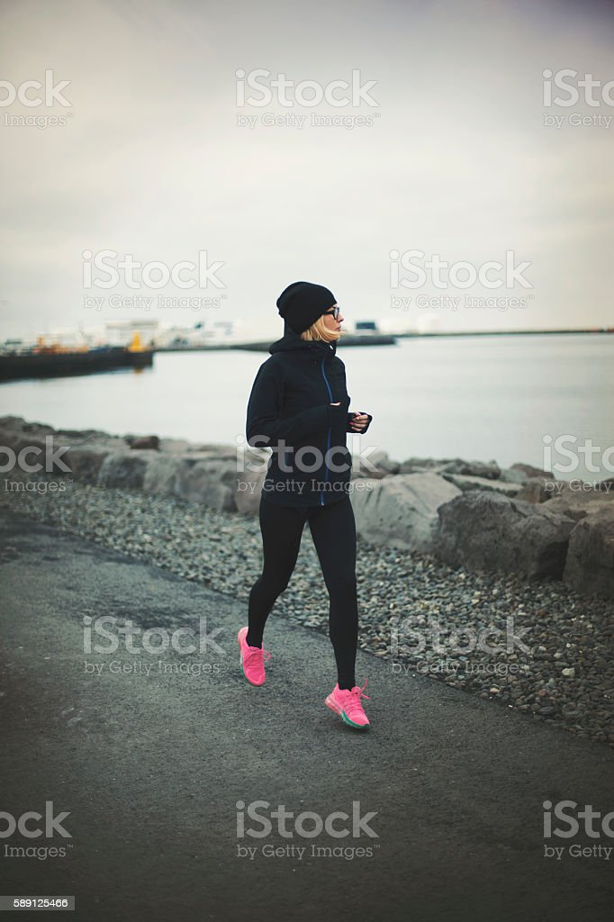 Young athlete woman running at the Iceland. stock photo