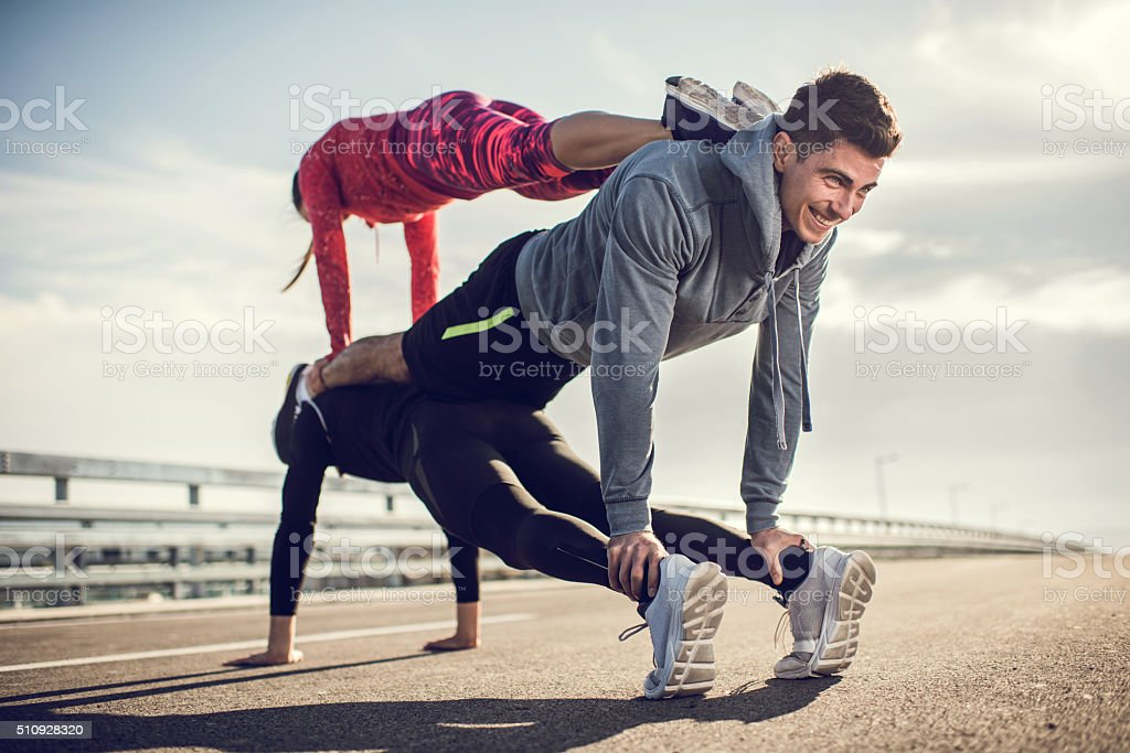 Young athletes doing balance exercises on a road. stock photo