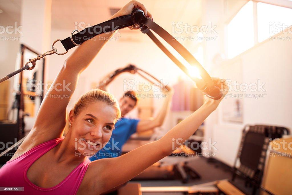 Young athletes doing stretching exercises on Pilates machines. stock photo