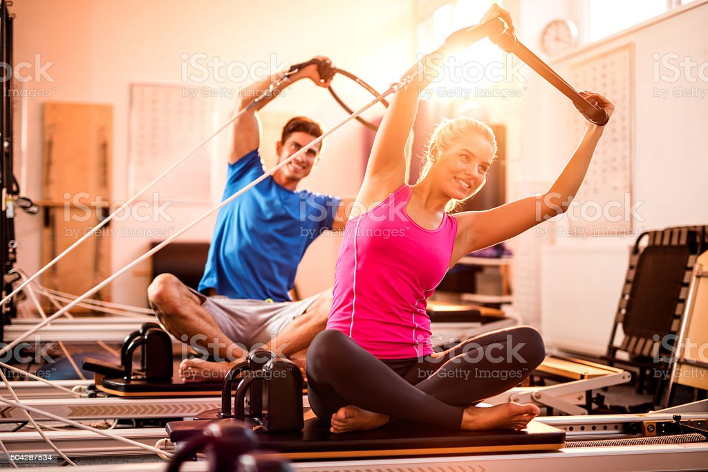 Young athletes doing stretching exercises on Pilates machines. stock photo