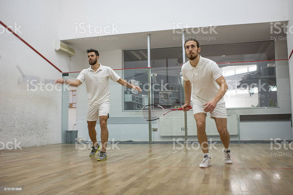 Young athletes in white playing squash on a court. stock photo