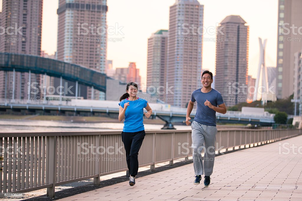 Young athletes jogging along river in cityscape stock photo