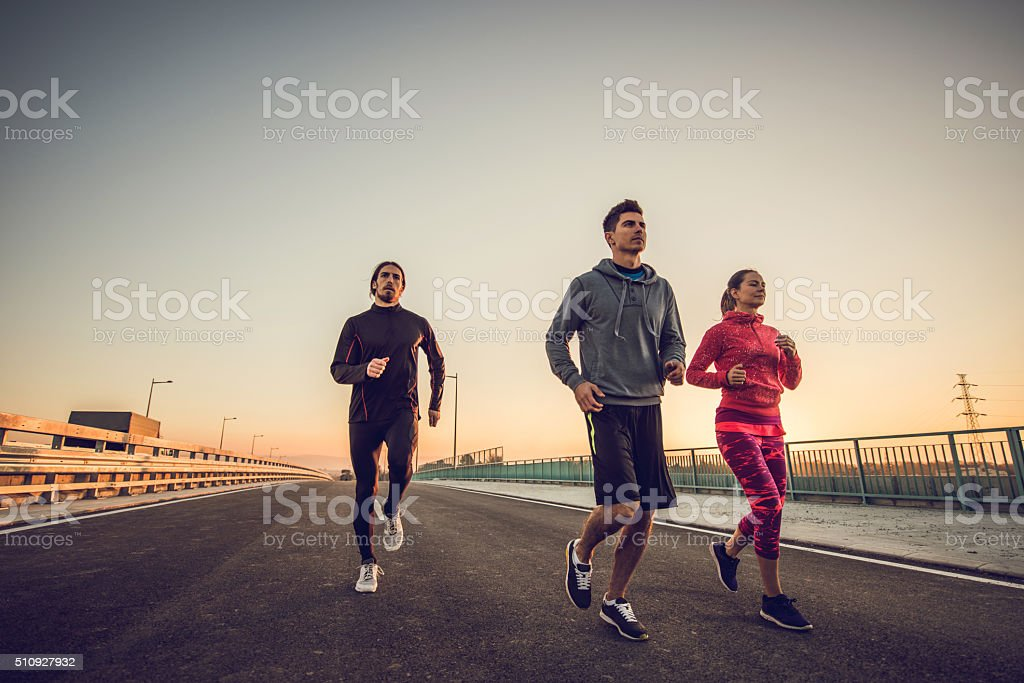 Young athletes running on a bridge at sunset. stock photo