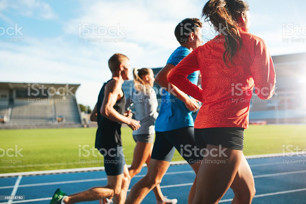 Young athletes running on race track in stadium stock photo