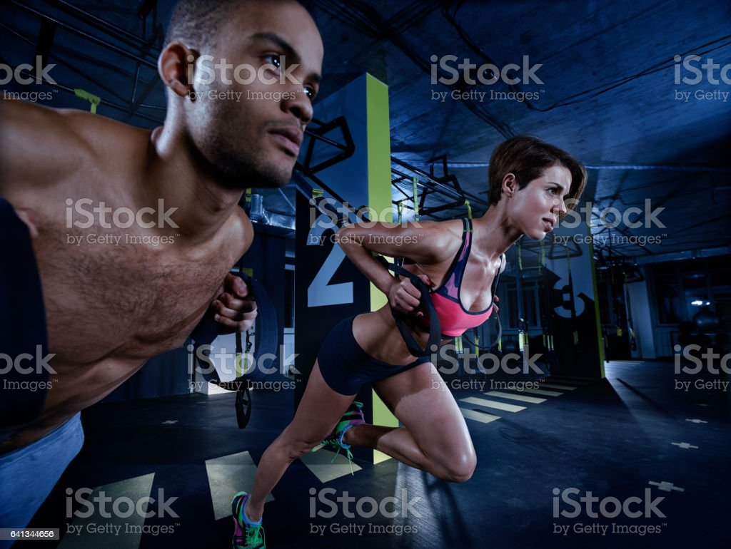 Young athletic couple doing push ups with trx straps stock photo