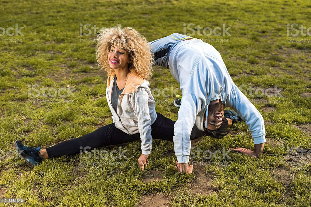 Young athletic couple doing stretching exercises in the park. stock photo