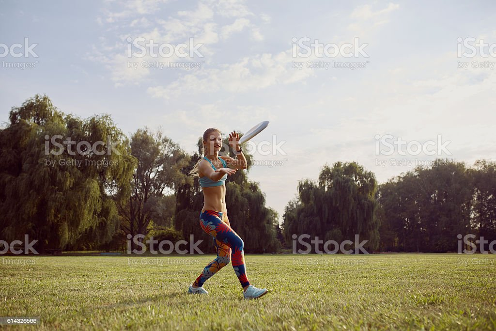 Young athletic girl playing with flying disc, ultimate stock photo