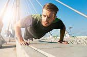 Young athletic man doing push-ups outdoors