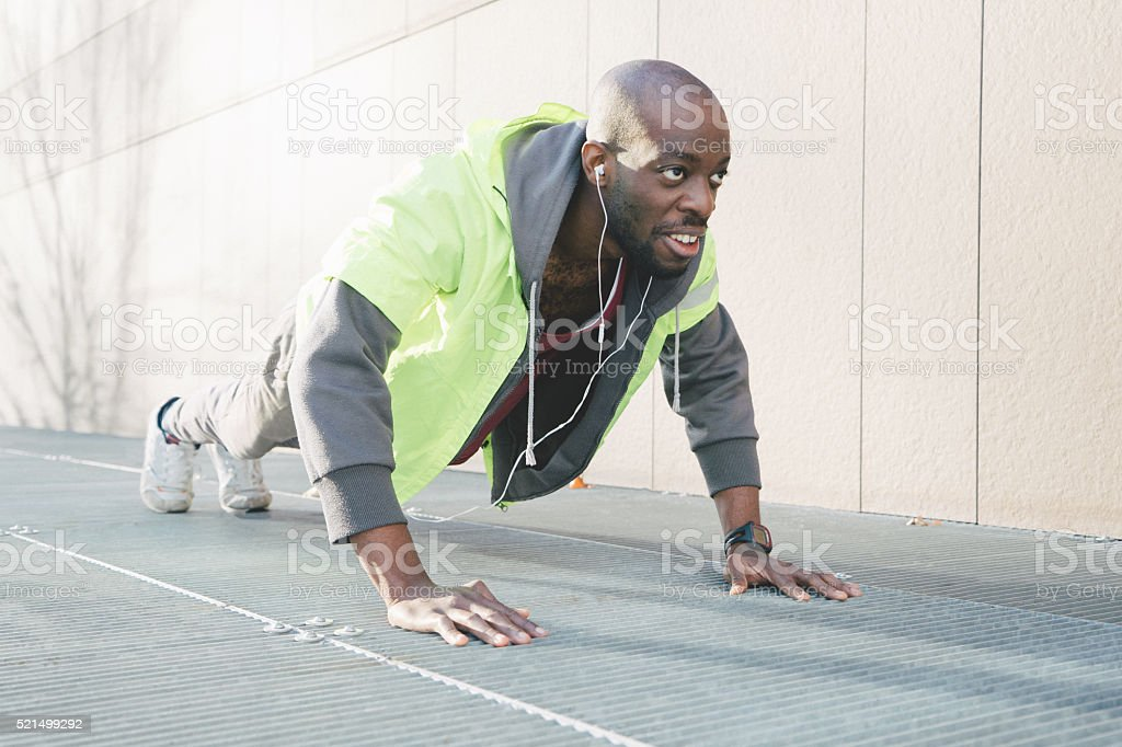 Young Athletic Man Exercising Outdoors Wearing A Fluorescent Jacket stock photo