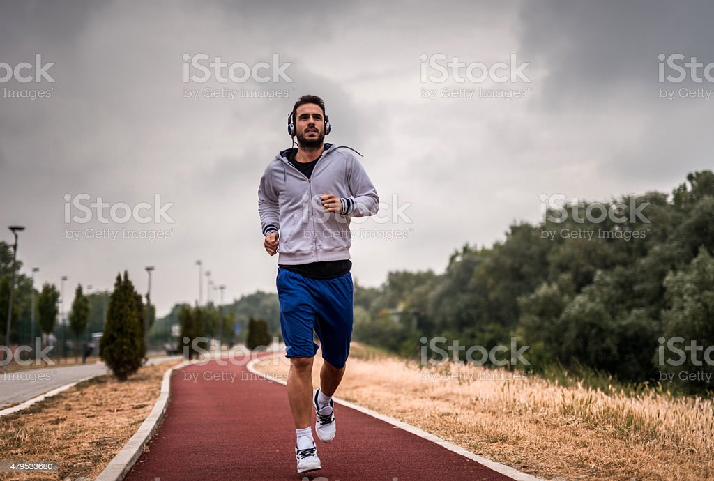Young athletic man jogging on sports track. stock photo