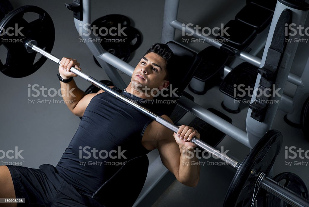 Young, athletic man lifting weights at the gym stock photo