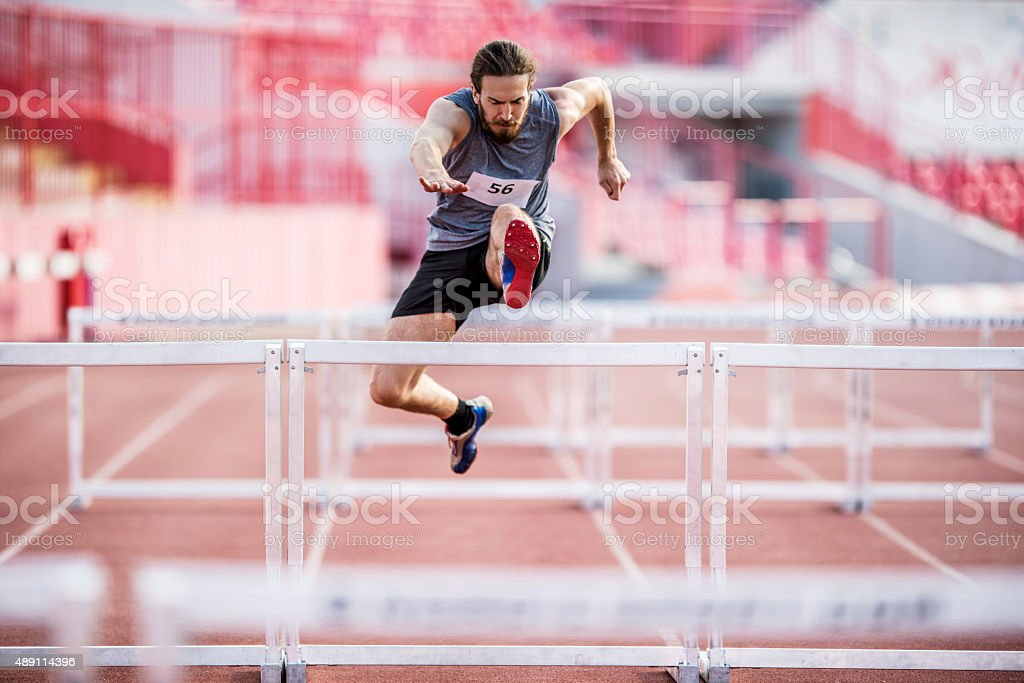 Young athletic man making an effort while jumping hurdles. stock photo