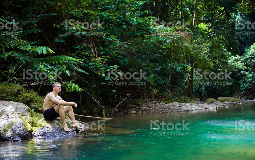Junge sportliche Mann sitzt an smaragdgrünen Dschungels pool Lizenzfreies stock-foto