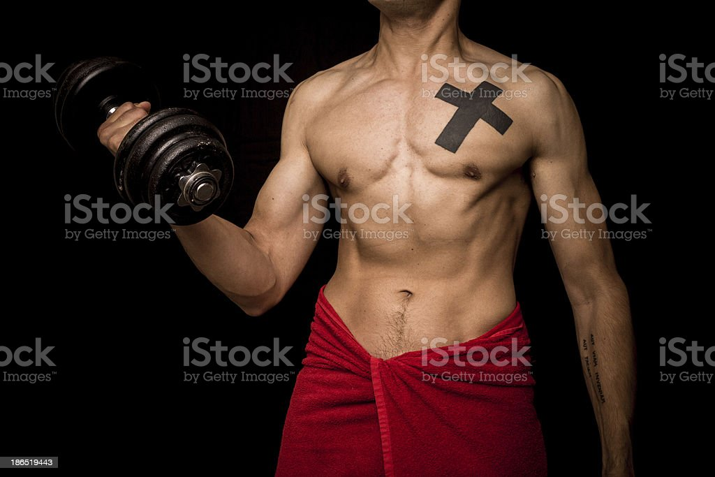 Young athletic shirtless man is working out with dumbbell royalty-free stock photo