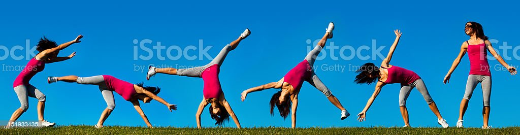 Young Athletic Woman Doing Cartwheel on Hilltop stock photo
