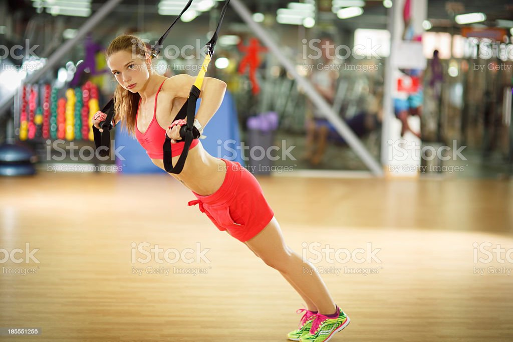 Young athletic woman doing push ups with trx straps royalty-free stock photo