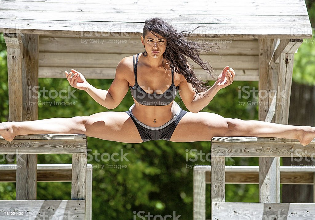 Young athletic woman doing the splits on wooden structures royalty-free stock photo
