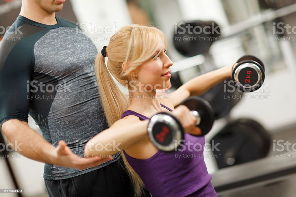 Young athletic woman having weight training with fitness instruc stock photo