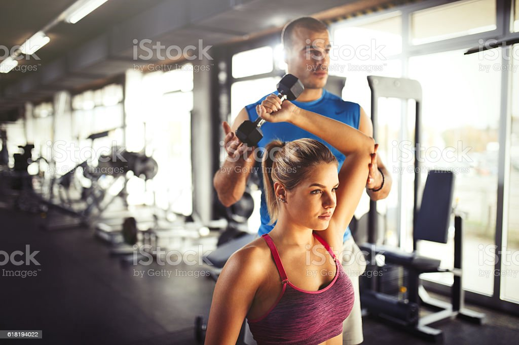 Young athletic woman having weight training with fitness instructor. stock photo
