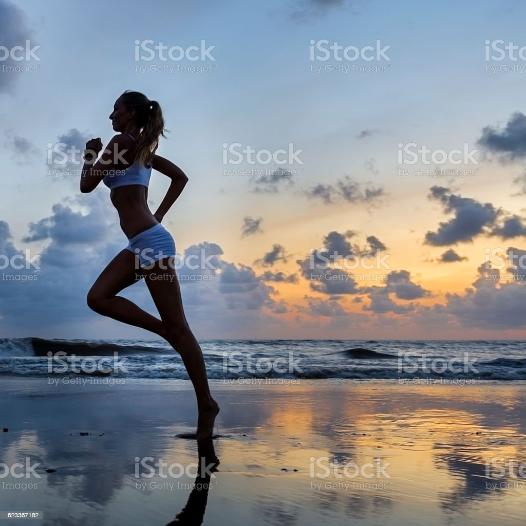 Young athletic woman jogging on the beach at sunset stock photo