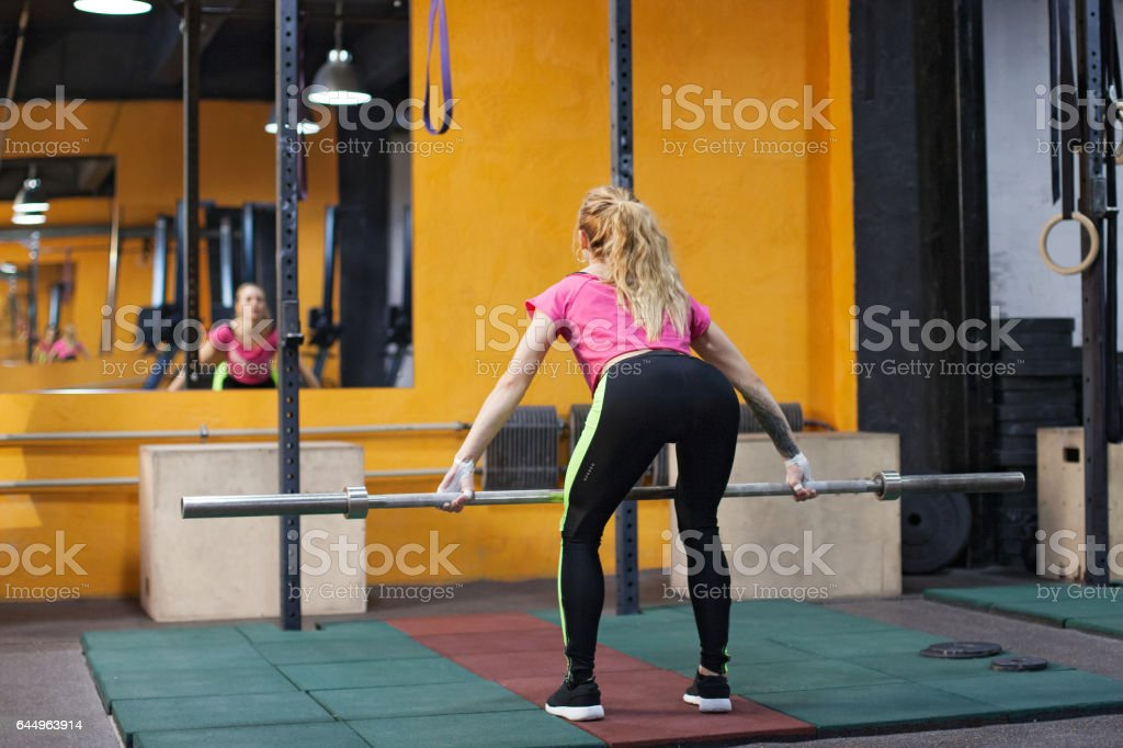 Young athletic woman performing dead lift stock photo