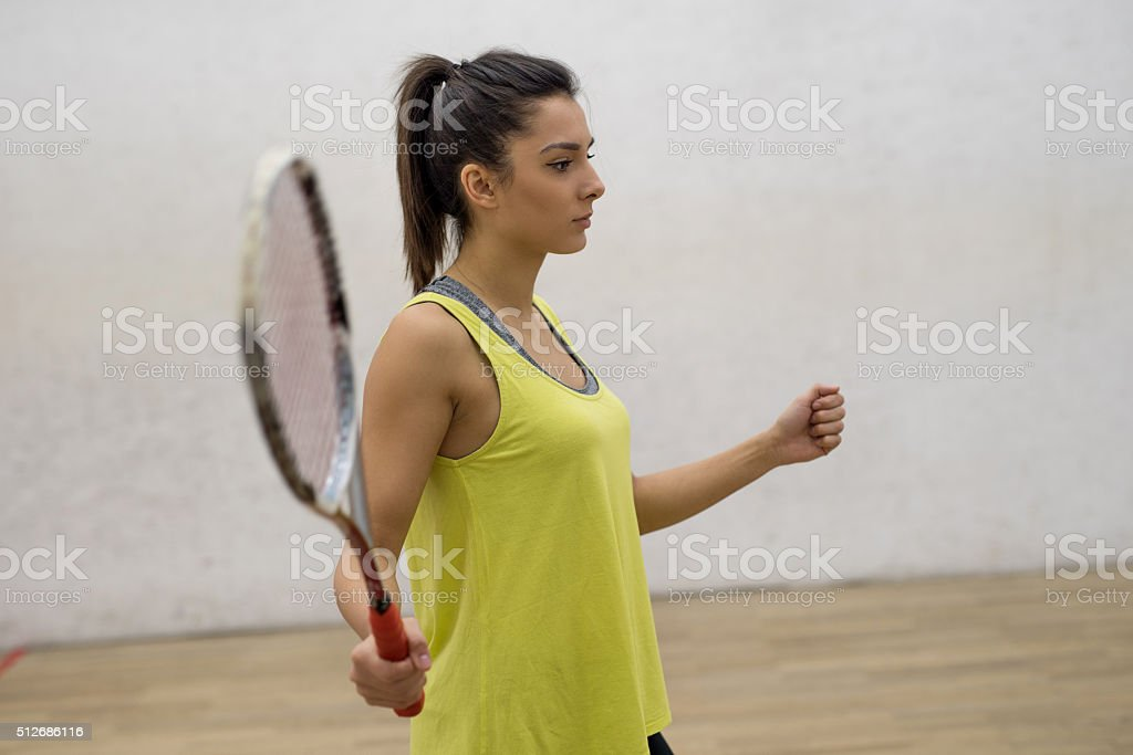 Young athletic woman playing squash on a court. stock photo