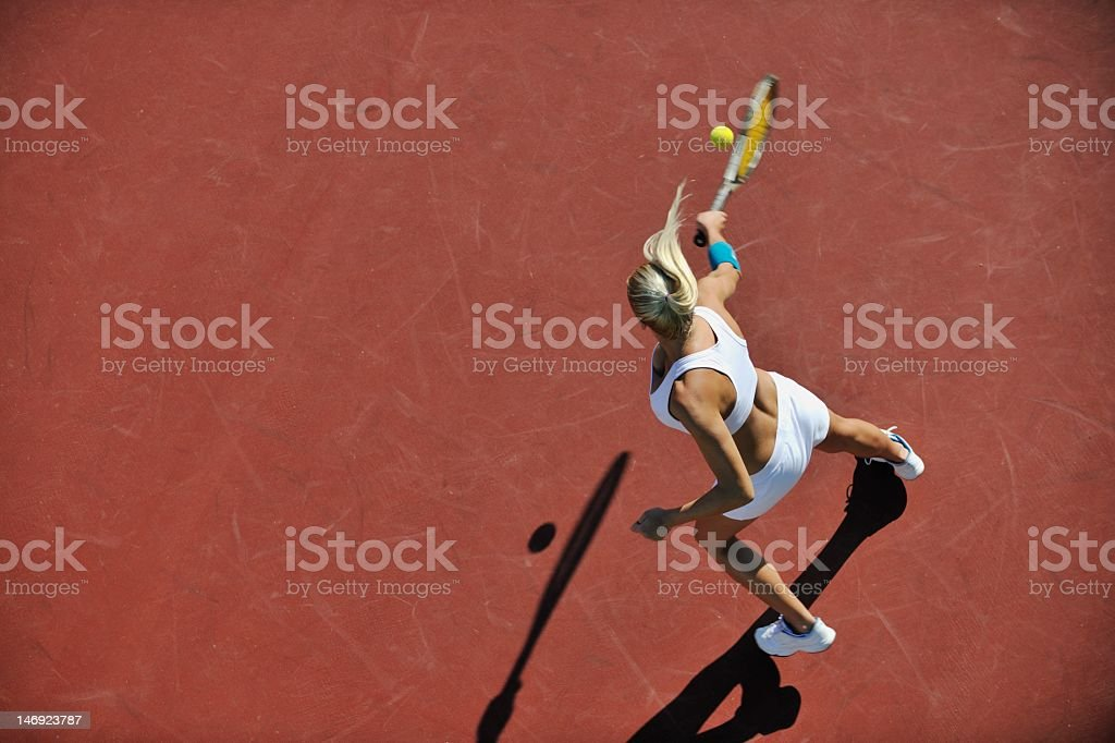A young athletic woman playing tennis outdoors stock photo