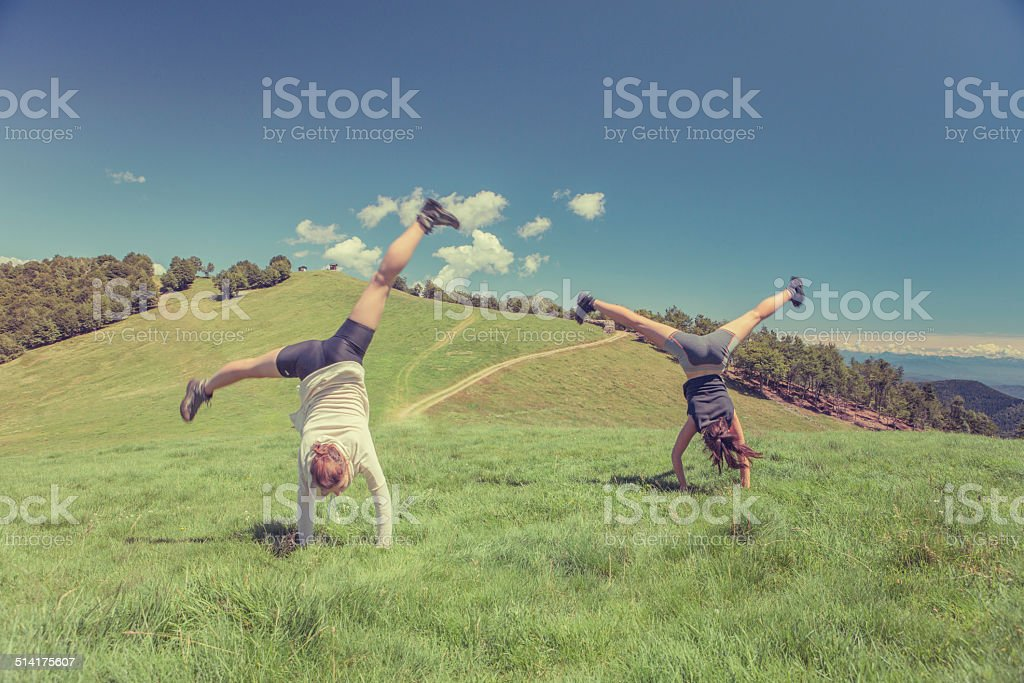 Young athletic women cartwheel in sunny day on mountain outdoor stock photo