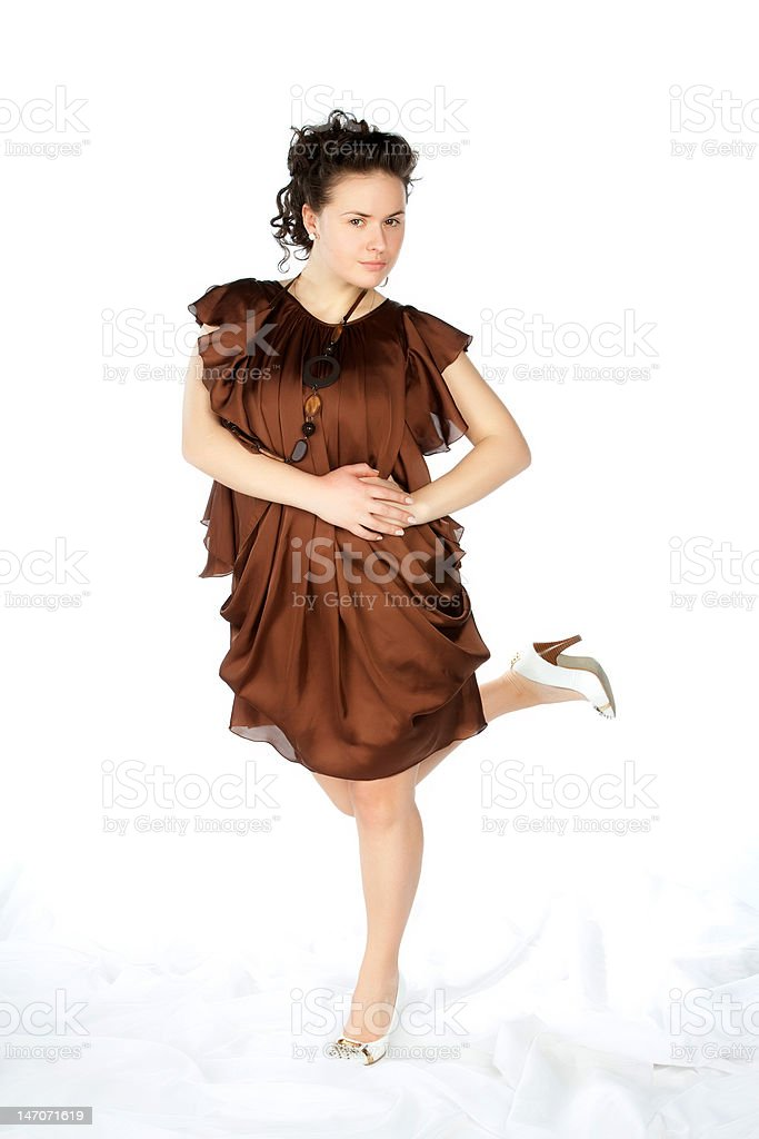 young atractive woman in brown dress hold one leg up royalty-free stock photo