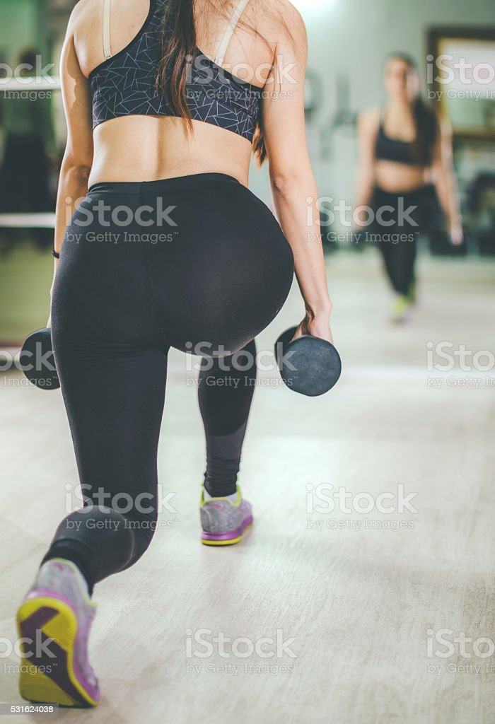young attracticve woman doing weighted lunges stock photo
