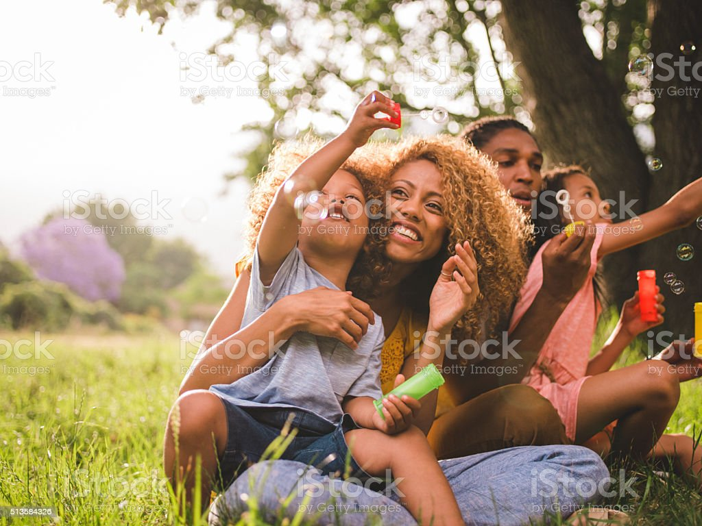 Young attractive african american family blowing bubbles in the stock photo