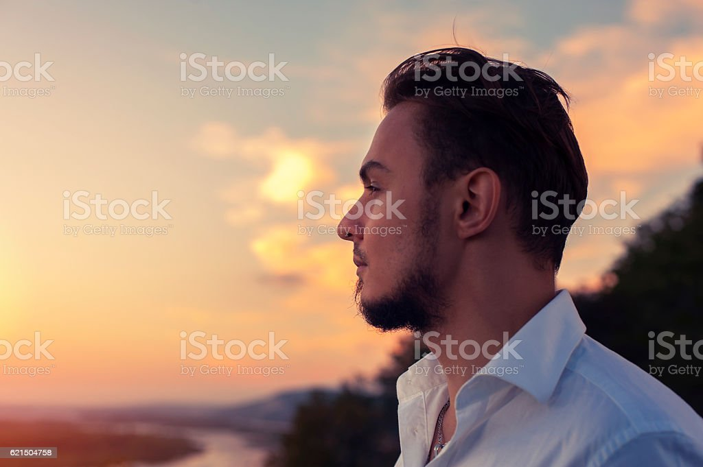 Young attractive bearded man standing outdoors stock photo