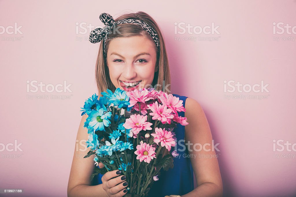 Young attractive beautiful woman smelling flowers. stock photo