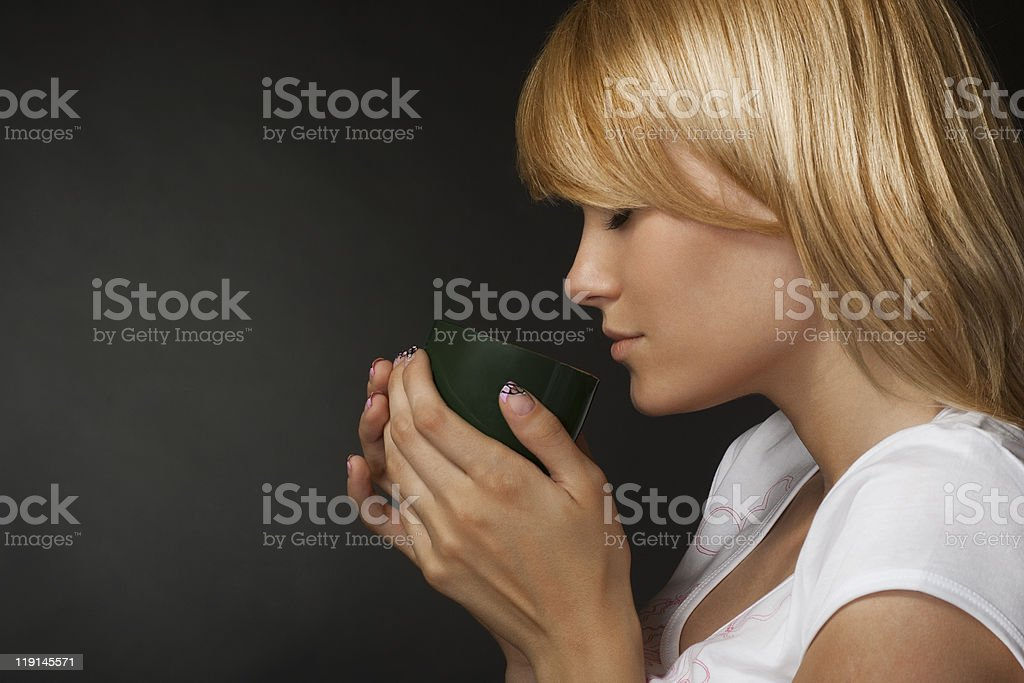 Young attractive blonde girl enjoys a cup of fragrant coffee stock photo