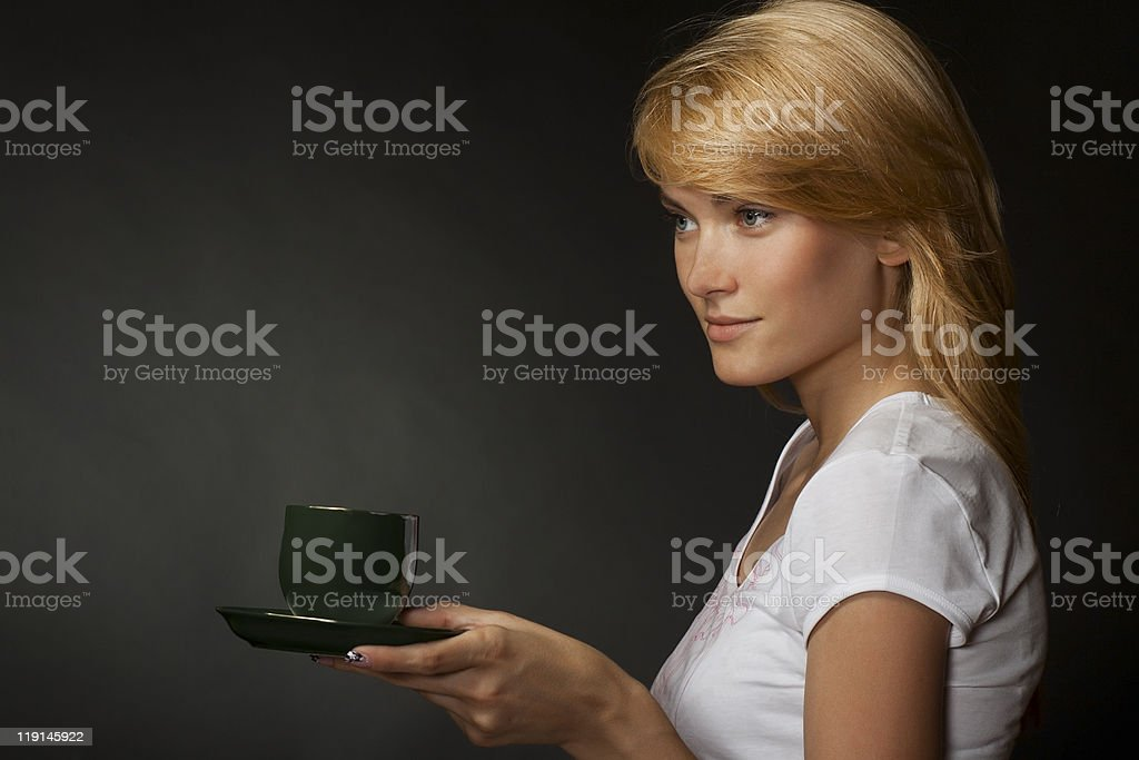Young attractive blonde girl enjoys a cup of fragrant coffee royalty-free stock photo