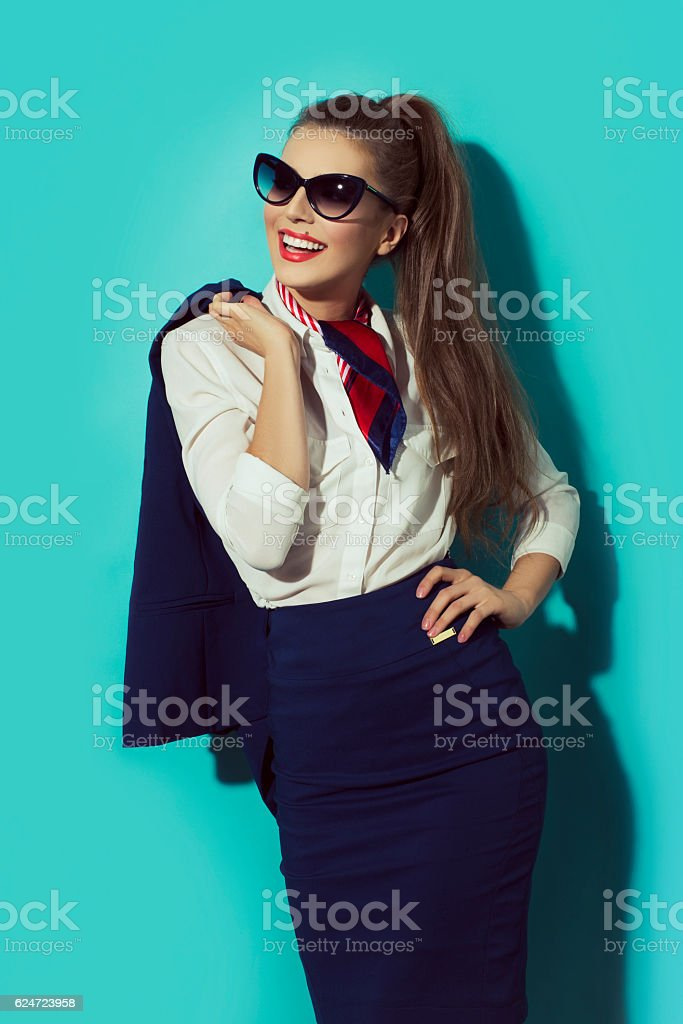 Young attractive business woman smiling putting jacket over the shoulder. stock photo