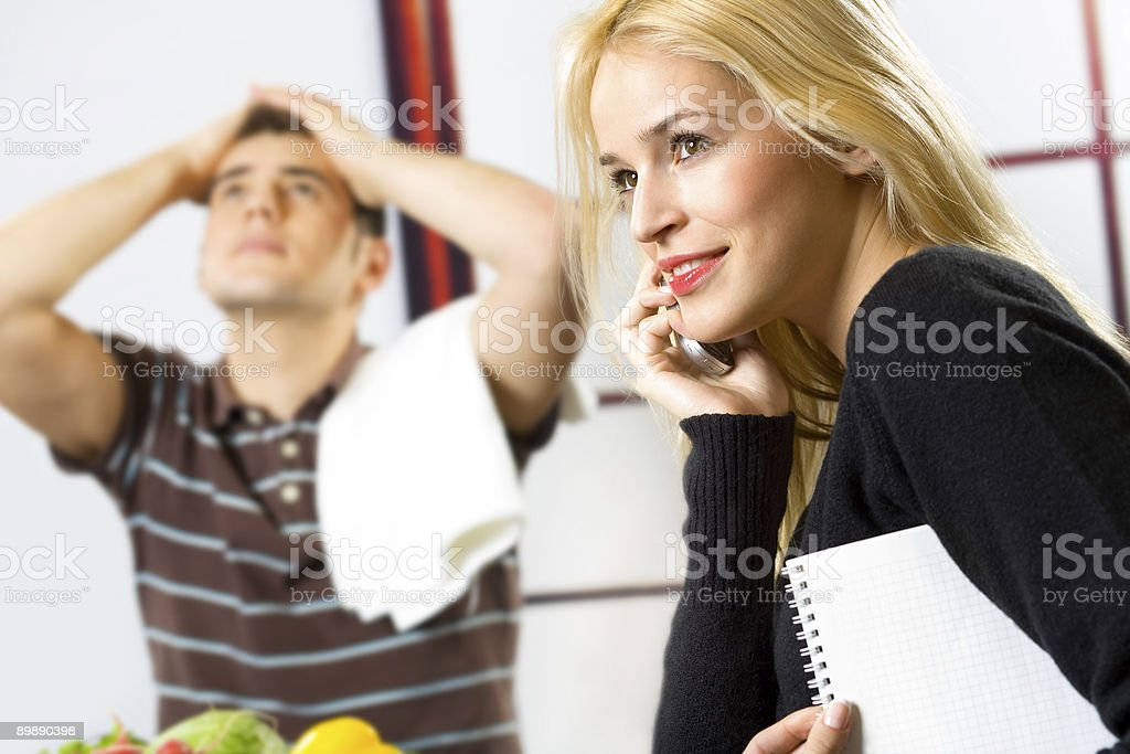 Young attractive businesswoman on cellphone and cooking man at kitchen royalty-free stock photo
