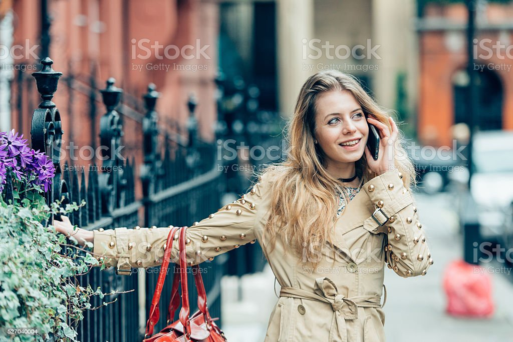 Young attractive businesswoman using a cell phone in the city. stock photo