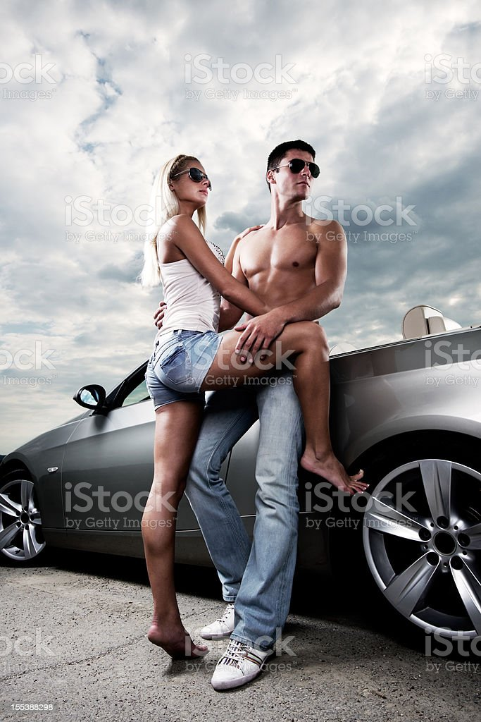 Young attractive couple leaning on their car. royalty-free stock photo