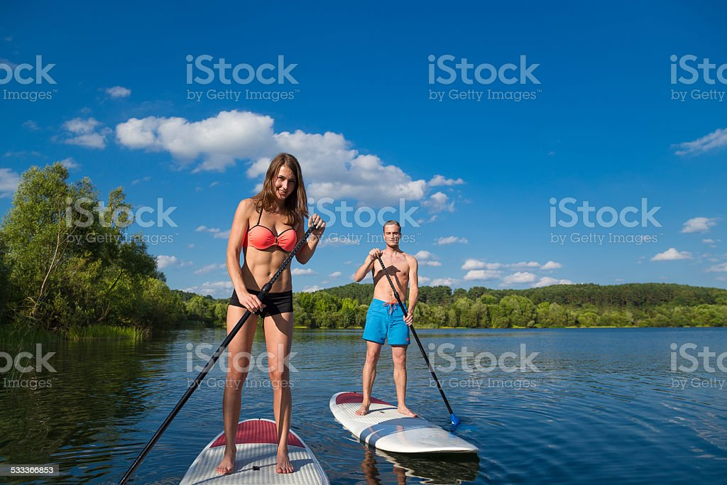 Young attractive couple on stand up paddle board stock photo