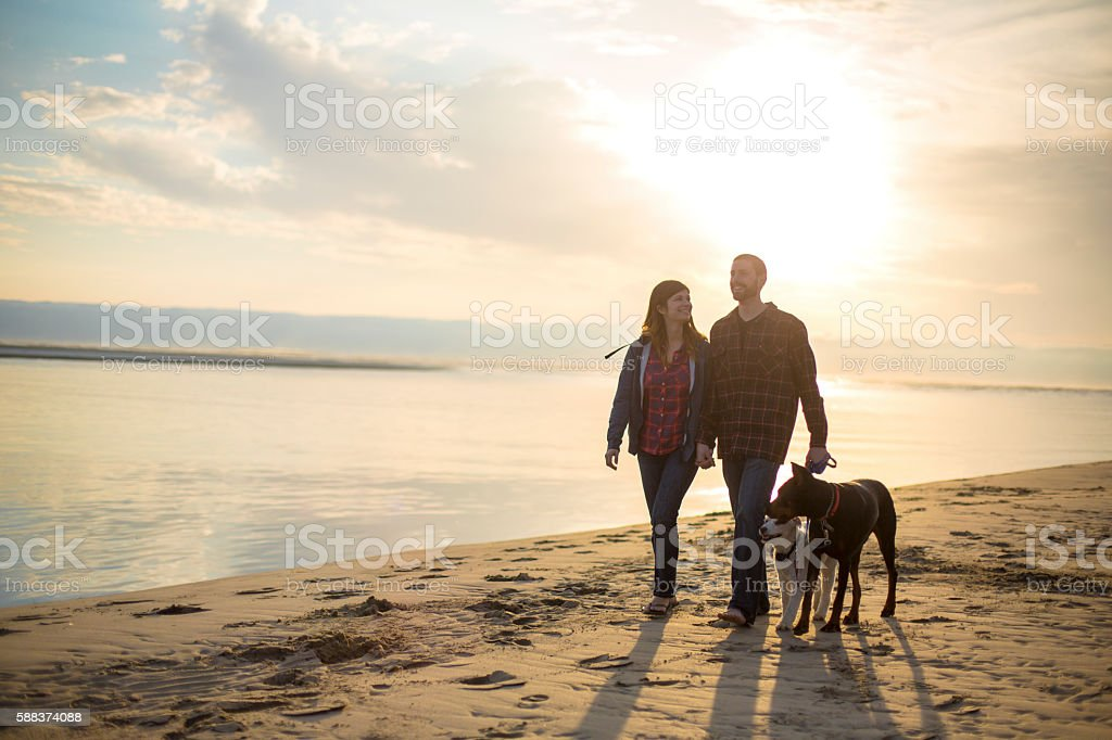 Young attractive couple talking on the beach at sunset stock photo