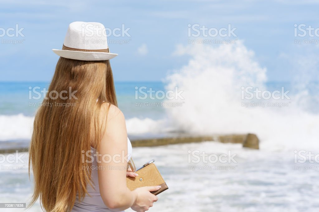 young attractive european woman with notepad and pen is staying close to beach of blue tropical sea on background of splashing strong wave stock photo