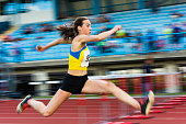 Young attractive female athlete at triple jump, pannig shot