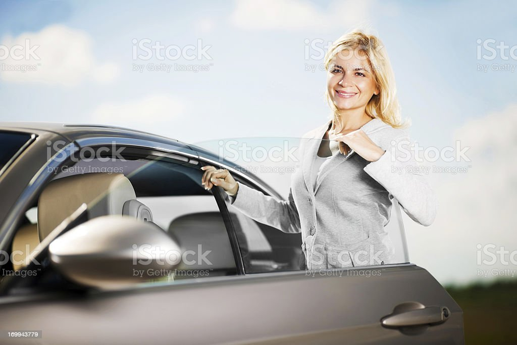 Young attractive female is opening her car door. royalty-free stock photo