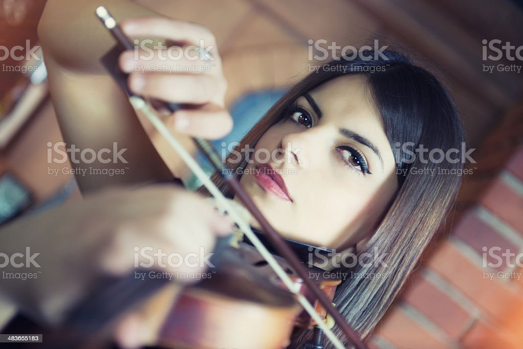 Young Attractive Female Playing her Violin with Expression stock photo