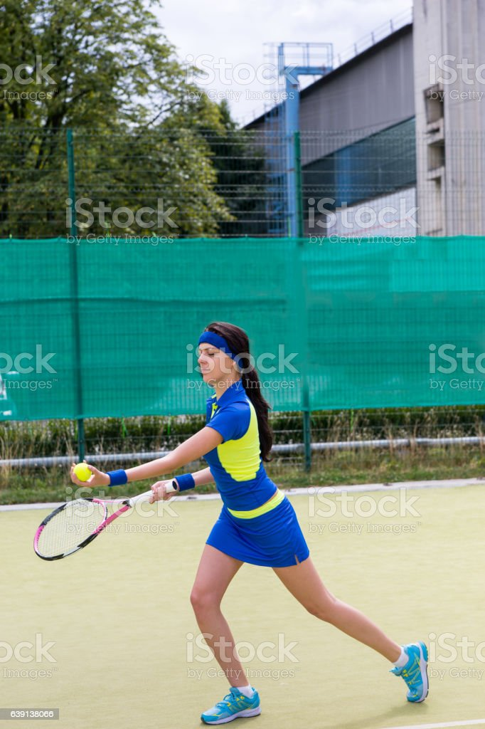 Young attractive female tennis player wearing a sportswear playing stock photo