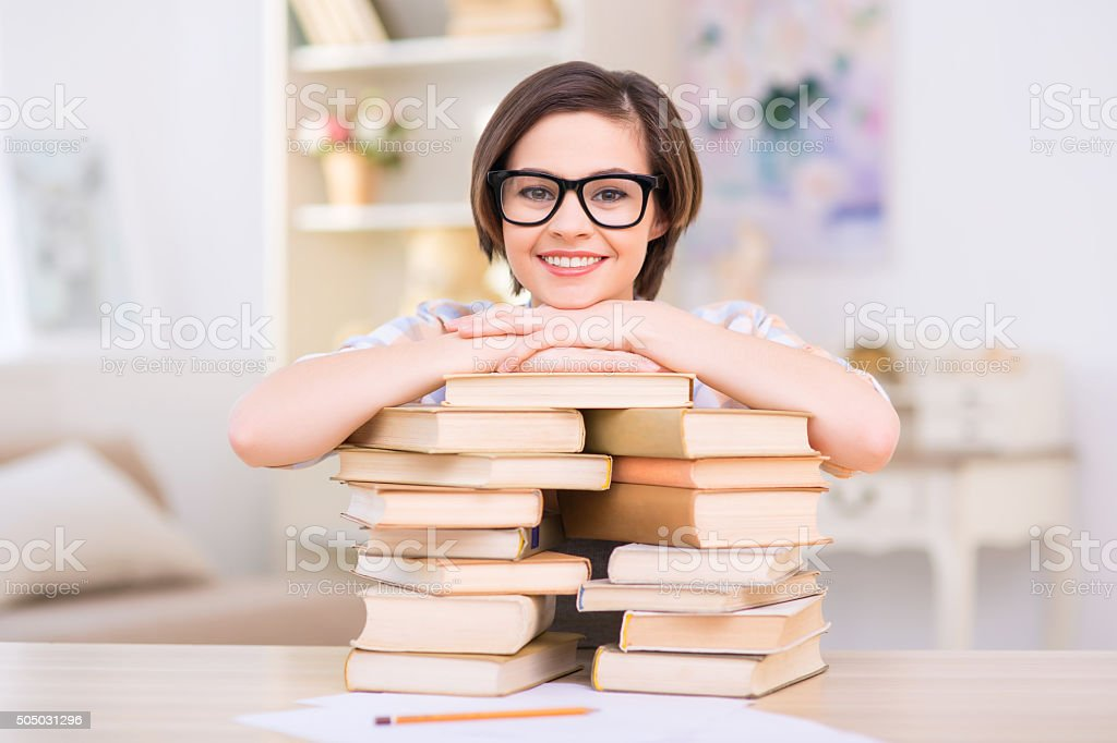 Young attractive girl is leaning on pile of books stock photo