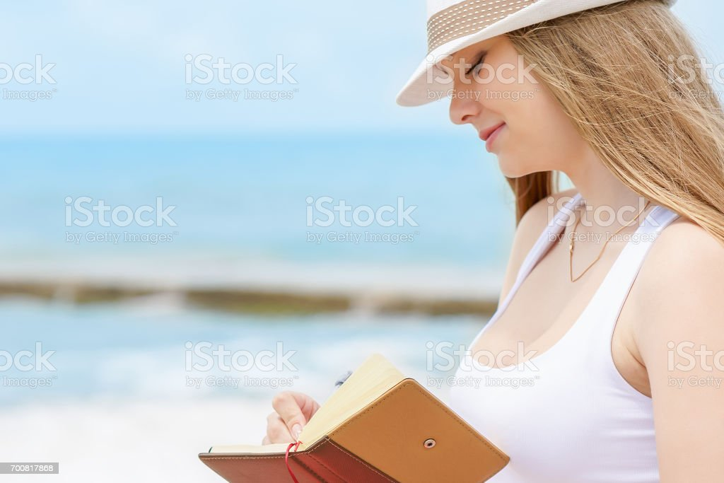 Young attractive girl with kind smile is writing some idea or letter in her note book by pen on background of blue sea stock photo